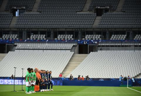 Saint-Etienne's players and Paris Saint-Germain's players line up in a near-empty stadium ahead of the French Cup final football match between Paris Saint-Germain (PSG) and Saint-Etienne (ASSE) on July 24, 2020, at the Stade de France in Saint-Denis, outside Paris. / AFP / FRANCK FIFE