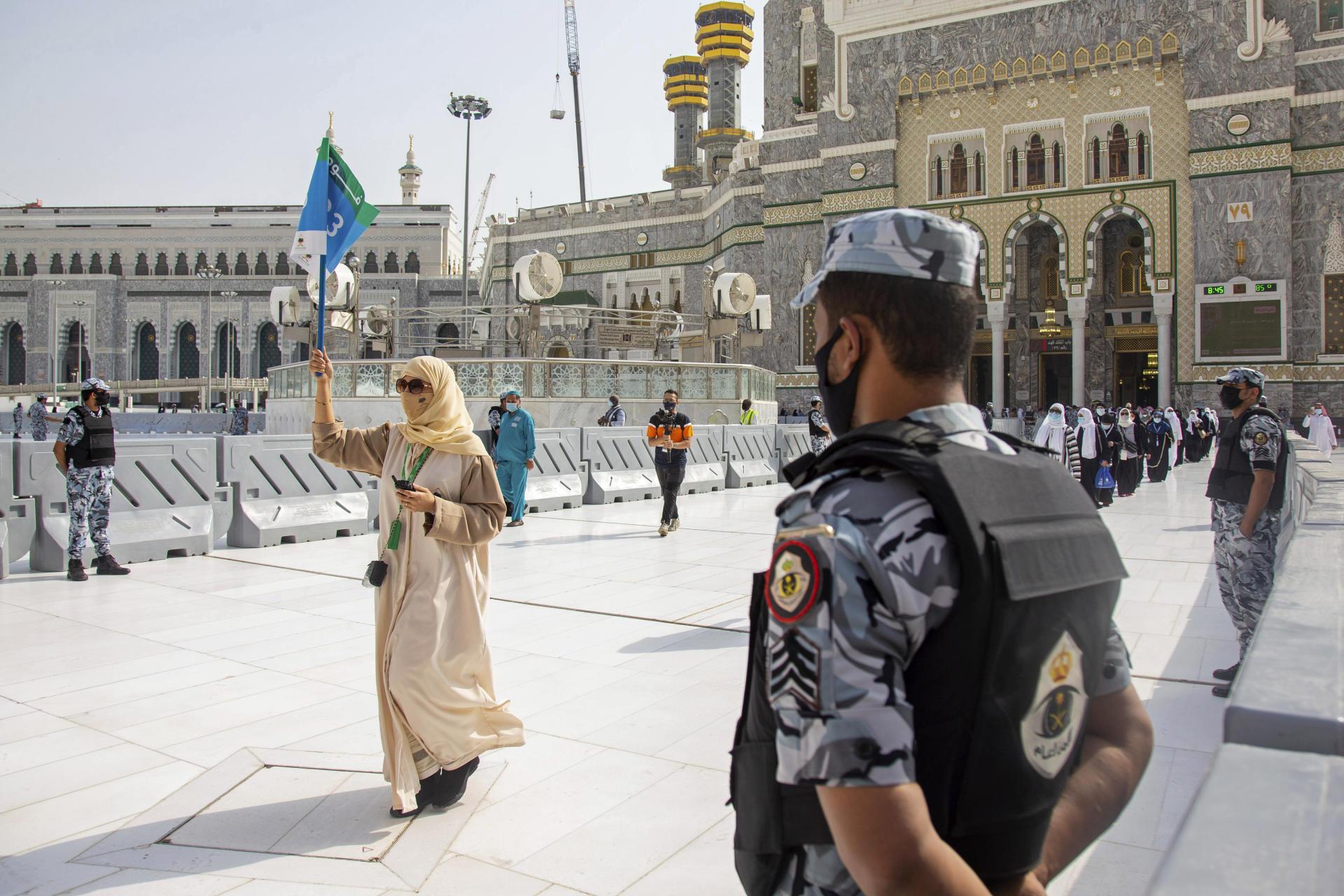 Les fidèles arrivent à la Grande Mosquée sous l'œil de policiers et autres officiels.