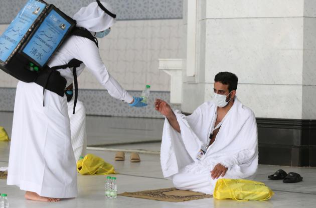 Un pèlerin reçoit une bouteille d'eau pendant qu'il prie à La Mecque.