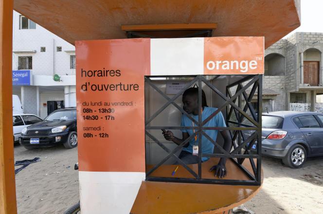 Un Sénégalais attend des clients sur un stand «Orange Money», à Ouakam, dans la banlieue de Dakar, le 7 juillet 2015.