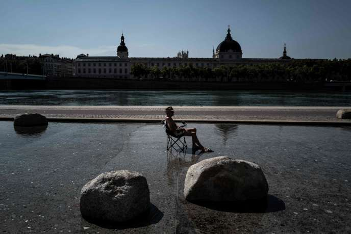 Un homme se rafraîchit, assis dans un bassin du centre de Lyon, le 30 juillet.