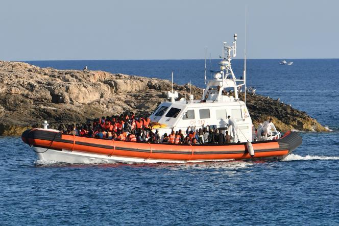Des migrants venus de Libye arrivent sur les côtes de l'île italienne de Lampedusa sur un bateau des gardes-côtes nationaux, vendredi 31juillet.