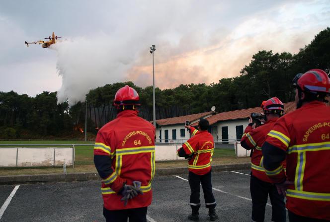 Les pompiers observent un avion Canadair alors qu'il tente d'éteindre un feu, à Anglet, dans le sud-ouest de la France, le 30 juillet.