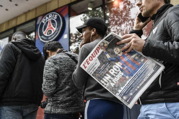Un supporter du PSG lit le journal« L'Equipe» en attendant l'ouverture de la boutique du club parisien, sur les Champs-Elysées, le 4 août 2017.