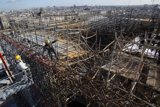 Des ouvriers installent des tubes sur l'échafaudage fondu, afin de le renforcer avant de le démanteler, à Notre-Dame de Paris, le 18 février.