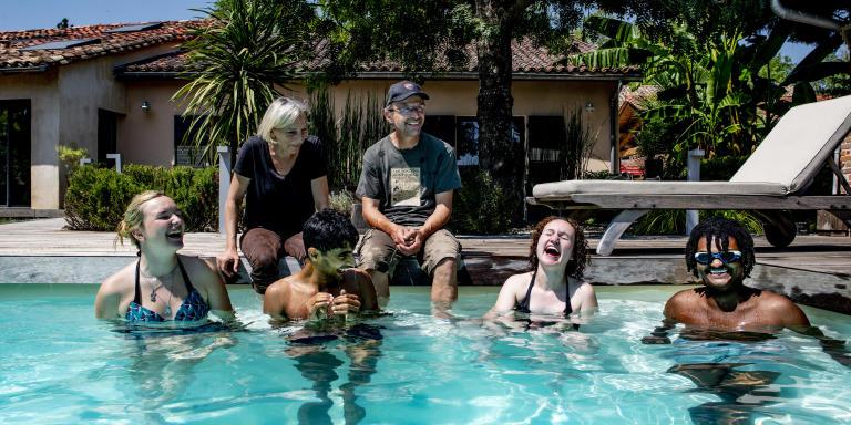 Valérie et Laurent Jorigné, 53 et 55 ans et leurs filles, Juliette 19 ans et Nikita, 27 ans se baignent en compagnie d'Ihtisham Arif et d'Adboulaye Barry, 17 ans (pakistanais et guinéen) dans la piscine de la maison familiale prés de Montauban.