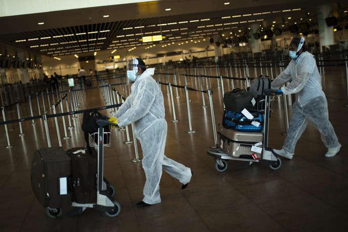 Des passagers, totalement protégés, à l'aéroport de Bruxelles, le 29juillet.