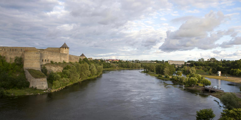 NARVA, ESTONIA, JULY 22, 2020: The Castle seen on the left belongs to Russian Federation. The Narva river in between is also the border between Estonia and Russian Federation. The right side of the river with the small bridge and walking pats belongs to Estonia.