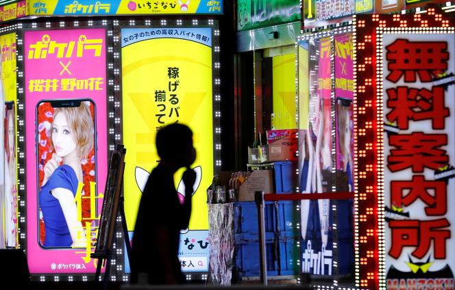 Un homme passe devant l'enseigne d'un bar du quartier de Kabukicho, à Tokyo, le 14 juillet.