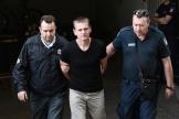 Alexander Vinnik, escorté par des policiers lors de son arrivée au palais de justice de Thessalonique, le 4 octobre 2017.
