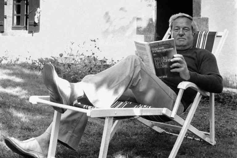 Le leader du Front national Jean-Marie Le Pen lit dans une chaise longue en septembre 1980 chez lui à la Trinité-sur-Mer, France.