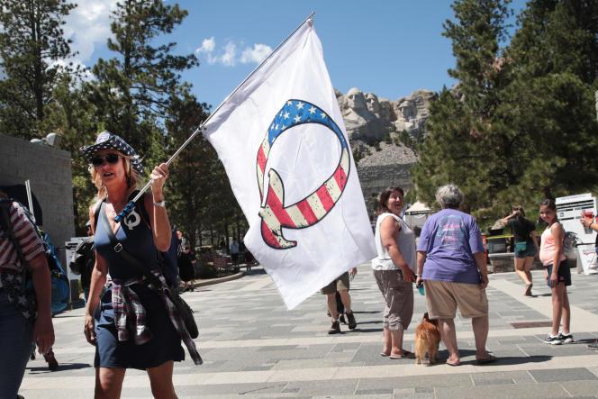 Une partisane de Donald Trump tient un drapeau QAnon devant le mont Rushmore, à Keystone, dans le Dakota du Sud, le 1er juillet.