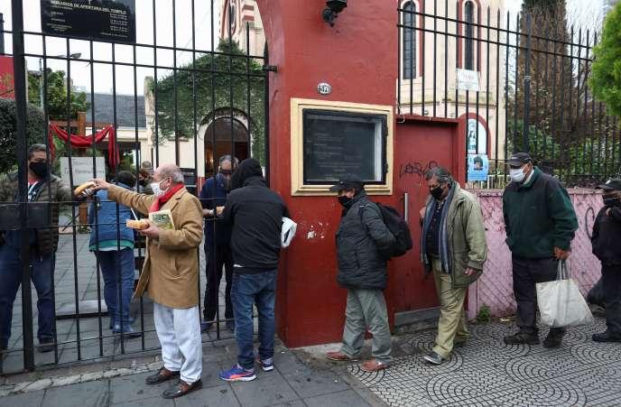 Des gens font la queue pour recevoir une ration de ragoût dans une soupe populaire organisée à l'église de Caacupe, à Buenos Aires, en Argentine, le 23 juillet.