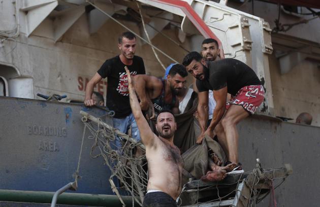 Des civils évacuent un marin blessé dans le port de Beyrouth, le 4 août.