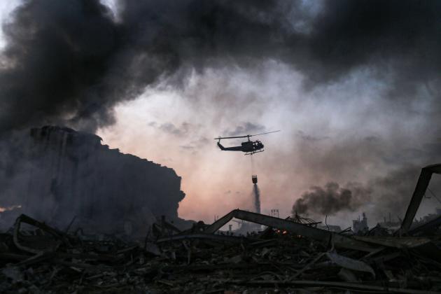 Un hélicoptère arrose le site de l'explosion, le 4 août à Beyrouth.