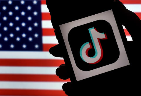 (FILES) In this file illustration photo taken on August 3, 2020 the social media application logo TikTok is displayed on the screen of an iPhone on an American flag background in Arlington, Virginia. The US is expanding its China-targeted Clean Network program to include Chinese-made cellphone apps and cloud computing services that it claims are security risks, Secretary of State Mike Pompeo announced on August 5, 2020. / AFP / Olivier DOULIERY