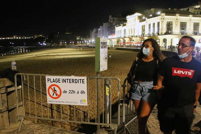 Des passants sur une plage de Biarritz, le 5 août.