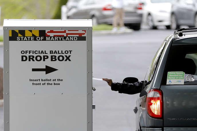Un automobiliste poste un bulletin de vote lors de l'élection spéciale du 7e district du Congrès, à Windsor Mill, dans le Maryland, le 28 avril 2020.