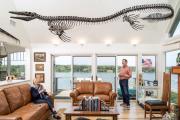 L'ophtalmologue américain Henry Kriegstein et son épouse, sous un fossile de mosasaure, dans leur maison du Massachusetts, en 2018.