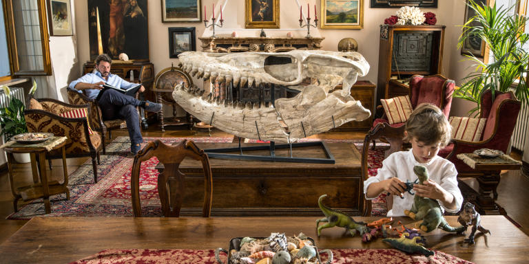 Motta Visconti, Italy - June 16th 2018 Francesco Invernizzi photograohed in the living room of his house in Motta Visconti, Italy. His son Edoardo is playing with little dinosaurs toys. Francesco is a movie and documentary producer. He has a big passion for natural history and wunderkammers (cabinet of curiosities). Francesco collects many different things, from art to fossils, from movies props to meteorites. He recently bought a skull of mosasaurs (you can see it in this picture). 'I have always wanted to have a dinosaur and finally, this year, I decided to buy one. The guy who sold me this skull told me that it's the biggest mosasaurs skull ever found. Now I keep it here in the living room, but I will move if to a special place in the house. I'm creating a special room for my collections of natural history items', he says.   Contacts:  Francesco Invernizzi  +39 333 4393383   francesco@magnitudo.it