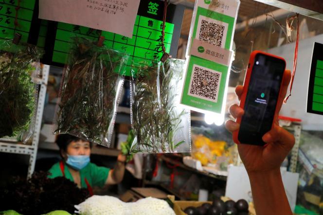 Une personne scanne le code QR des services de paiement numérique WeChat Pay sur un marché à Pékin, le 8 août.