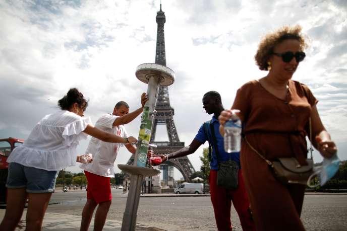 Des personnes se rafraîchissent à une fontaine à Paris, le 8 août.
