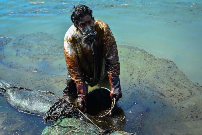 Un homme tente de récupérer du pétrole dans les eaux de l'île Maurice, le 8 août.