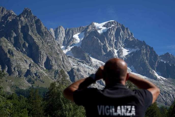 Un agent de sécurité regarde à travers des jumelles le glacier de Planpincieux dans le village de Courmayeur, Val Ferret, au nord-ouest de l'Italie, le 8 août.