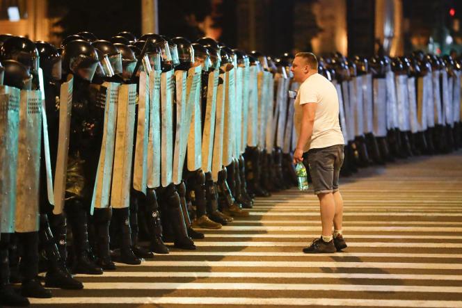Barrage de police devant lessupporteurs de l'opposition biélorusse qui manifestent après la fermeture des votes, le 9 août à Minsk.