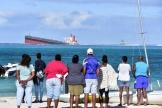 Des passants observent levraquier Wakashio échoué dans l'océan Indien, au sud-est de l'île Maurice, le 6 août.