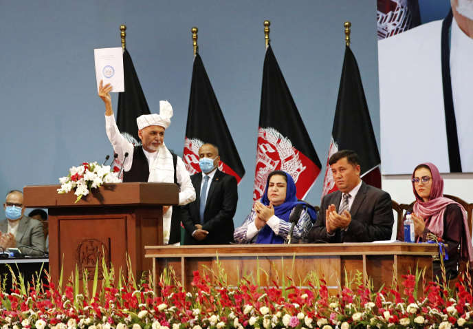Le président afghan Ashraf Ghani brandit la résolution sur les prisonniers talibans obtenue le dernier jour de réunion du conseil traditionnel, à Kaboul, le 9 août.