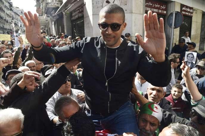 Khaled Drareni, porté par des manifestants après avoir été brièvement détenu par les forces de sécurité à Alger, le 6 mars 2020.