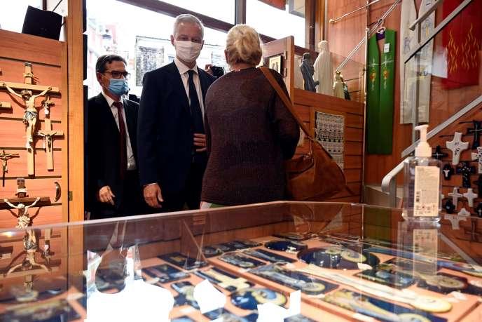 Le ministre de l'économie et des finances, Bruno Le Maire (au centre), visite une boutique de souvenirs près du sanctuaire de Notre-Dame de Lourdes, le 10 août, dans le sud-ouest de la France.
