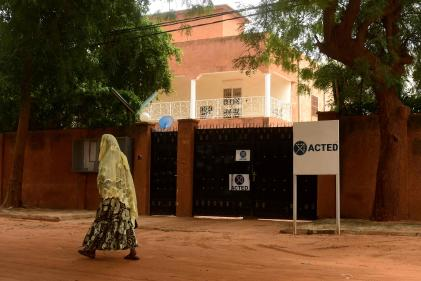 A woman walks past the gates of the local office of the French aid group ACTED in Niamey on August 10, 2020. / AFP / BOUREIMA HAMA