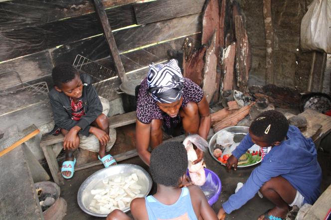 Entourée de sa fille et de ses petites-filles, Hélène Evelyne Ngo Nemi, 48 ans, prépare un«mbongo tchobi» à Dibamba, au Cameroun.