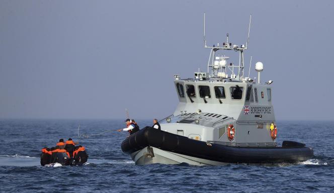 Un navire de l'agence responsable des opérations de contrôle frontalier aide un groupe de personnes considérées comme des migrants à bord de leur canot pneumatique dans la Manche, le 10 août 2020.