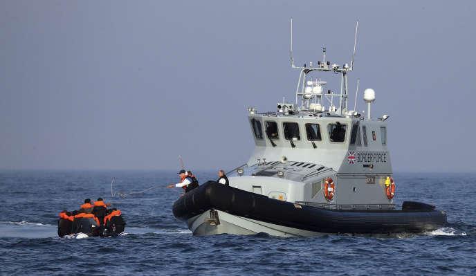 Un navire de la Force frontalière aide un groupe de personnes soupçonnées d'être des migrants à bord depuis leur canot pneumatique dans la Manche, le 10 août.