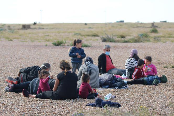 Un groupe de migrants se repose sur la plage en attendant les responsables des forces frontalières britanniques à Dungeness, dans le sud de l'Angleterre, le 6 août.