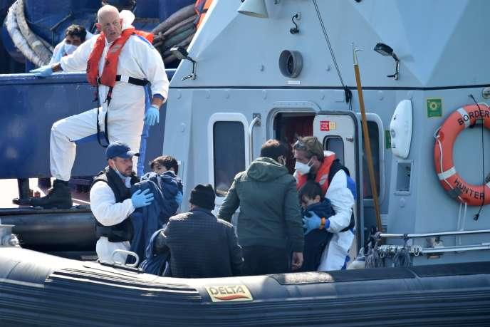 Les agents des forces frontalières britanniques aident les migrants avec des enfants, dans le port de Douvres, sur la côte sud-est de l'Angleterre, le 9 août .