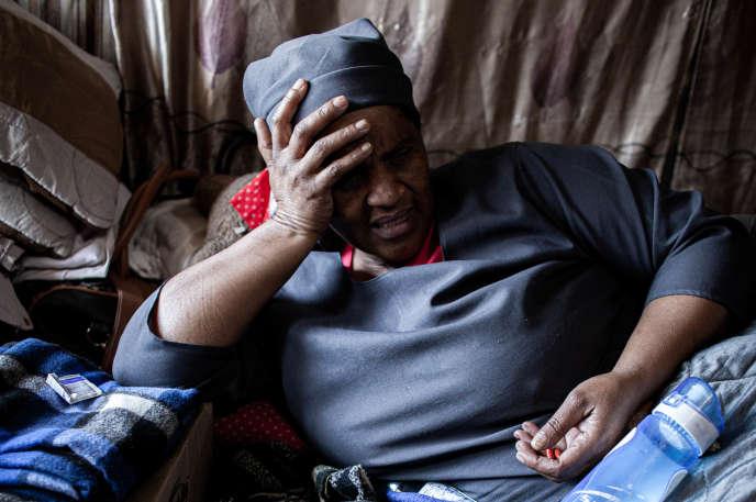 Sara Nomphelo, 50 ans, sur son lit, dans l'unique pièce de sa maison, le 15 juillet dans le township d'Alexandra (Afrique du Sud).