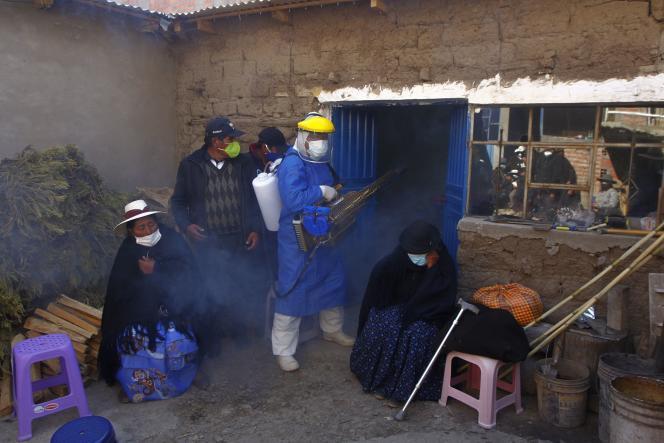 Un employé funéraire désinfecte la maison d'une victime du Covid-19 dans le village péruvien d'Acora, près de la frontière avec la Bolivie, le 9 août.