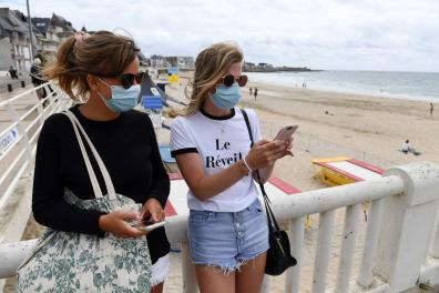 People wearing mask stand near the beach of Quiberon, on July 27, 2020, western France. - French officials have ordered nighttime curfews for beaches in the Brittany resort of Quiberon on the Atlantic coast, after a fast-spreading COVID-19 cluster emerged last week. (Photo by Fred TANNEAU / AFP)