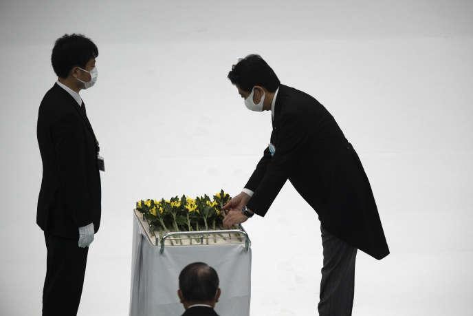 Le premier ministre japonais, Shinzo Abe (à droite), pose une gerbe de fleurs lors des cérémonies marquant la fin de la deuxième guerre mondiale, samedi 15 août 2020 à Tokyo.