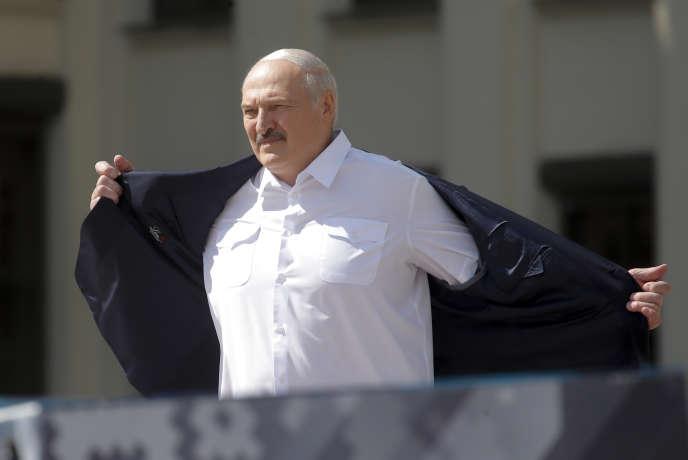 Le président Alexander Lukachenko enlève sa veste avant de s'adresser à ses partisans à Minsk le dimanche 16 août.