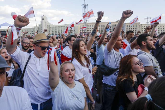 Les manifestants agitent l'ancien drapeau national pour manifester contre le gouvernement le 16 août à Minsk.
