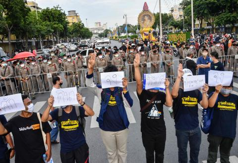 Anti-government protesters hold up three-finger salutes and signs during a pro-democracy rally as police look on in Bangkok on August 16, 2020. Protesters gathered for a rally in Bangkok on August 16 against the government as tensions rose in the kingdom after the arrest of three activists leading the pro-democracy movement. / AFP / Mladen ANTONOV