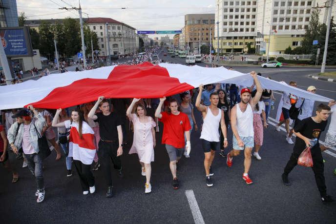 L'ancien drapeau national est déployé lors d'un rassemblement de l'opposition le 16 août à Minsk (Biélorussie).
