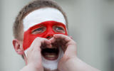 A man with a face painted with the old Belarusian national flag, shouts during opposition rally in front of the government building of Minsk, Belarus, Sunday, Aug. 16, 2020. Opposition supporters whose protests have convulsed the country for a week aim to hold a major march in the capital of Belarus. Protests began late on Aug. 9 at the closing of presidential elections. (AP Photo/Dmitri Lovetsky)
