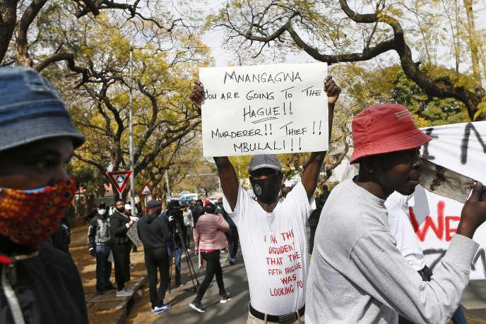 Des manifestants brandissent des pancartes contre la corruption de l'Etat et la détérioration de l'économie du Zimbabwe devant l'ambassade du pays à Pretoria, en Afrique du Sud, le 7 août 2020.
