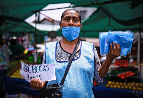 MEXICO CITY, MEXICO - APRIL 19: Isabel, a domestic worker who lost her job, sells face masks at a mobile market in the Piedad Narvarte neighborhood on April 19, 2020 in Mexico City, Mexico. Mexico is under health emergency, which implies that only essential activities are permitted. Government suggested population to stay at home but quarantine is not obligatory as there is major concern about the economic activity. Hugo Lopez-Gatell Undersecretary of Prevention and Health Promotion announced the extension of the measures until at least, May 30 in those cities with a bigger risk and number of contagion. (Photo by Manuel Velasquez/Getty Images)